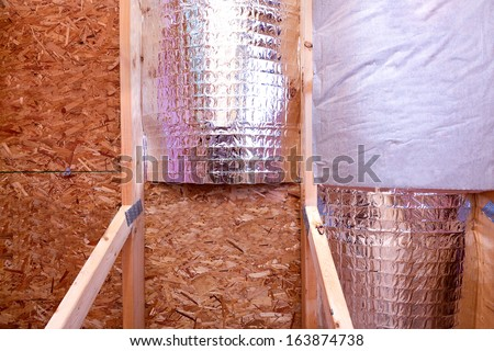 Attic insulating with reflective heat barrier and fiberglass cold barrier between the attic joists, work is ongoing, inside gable and joist view - stock photo