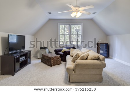 Attic man cave with furniture and flat screen tv - stock photo
