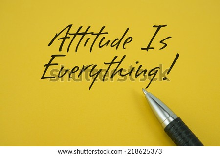 Attitude Is Everything! note with pen on yellow background