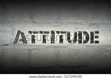 attitude stencil print on the grunge white brick wall
