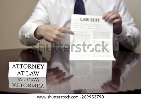 Attorney at Law sitting at desk holding Lawsuit suit - stock photo