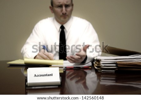 Attorney at Law sitting at desk holding pen with files - stock photo