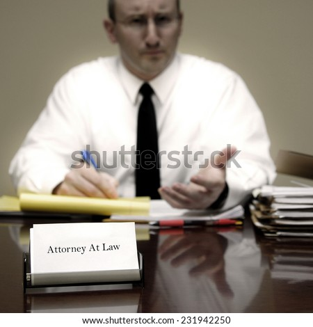 Attorney at Law sitting at desk holding pen with files