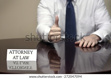 Attorney at Law sitting at deskwith thumbs up for success or good job - stock photo