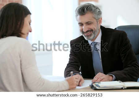 Attorney meeting client in office for signature