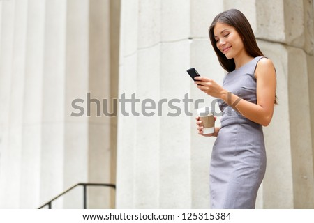 Attorney - young asian woman lawyer looking at mobile smartphone and drinking coffee from disposable paper cup. Young multiethnic female professional in the city in front of courthouse. - stock photo