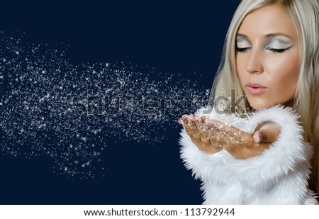 Attracive girl in santa cloth blowing snow from hands - stock photo