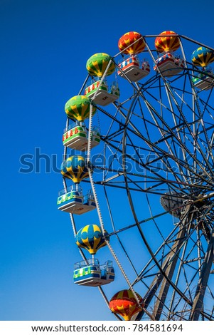 Attraction of a Ferris wheel against a blue sky background. The gondolas are decorated in the form of balloons.