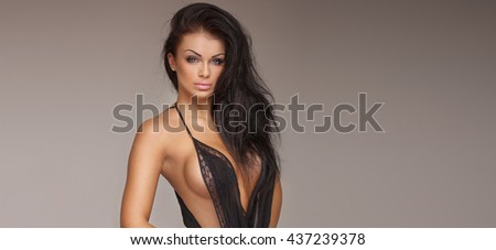 Attractive adult brunette lady posing in black sexy lingerie, looking at camera. Indoor photo. - stock photo