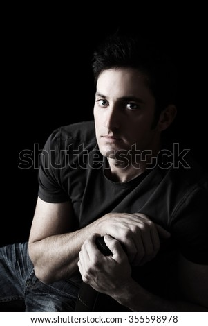 Attractive adult brunette male model against black background - stock photo
