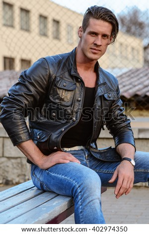 attractive adult man sitting alone on bench - stock photo