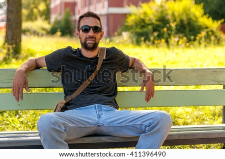 attractive adult man sitting alone on bench in park - stock photo