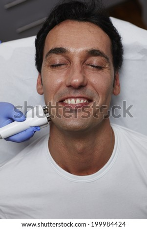 Attractive  adult patient having a laser skin treatment in a skincare clinic, handsome man in white t-shirt at rejuvenation procedure - stock photo