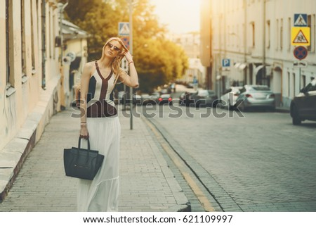 Attractive adult tall caucasian woman in long white skirt, sunglasses and with bag is fixing her hair while standing on street during sunny summer day with copy space for text or your logo