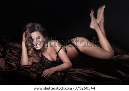 Attractive adult woman posing in elegant black lingerie, lying in bed. - stock photo