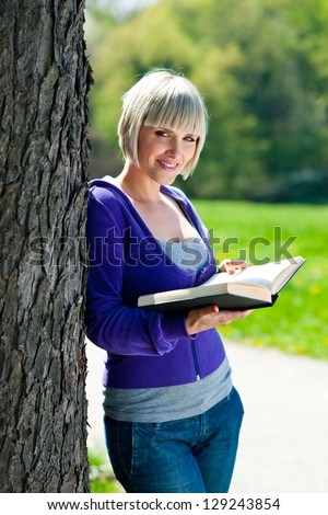 attractive adult woman with book outside - stock photo