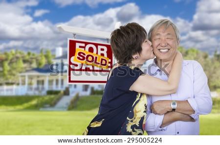 Attractive Affectionate Senior Chinese Couple In Front of Beautiful House and Sold For Sale Real Estate Sign. - stock photo