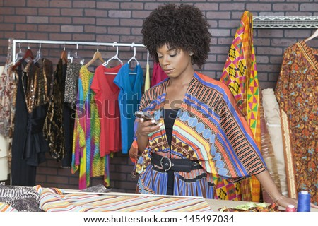 Attractive African American female fashion designer using cell phone - stock photo