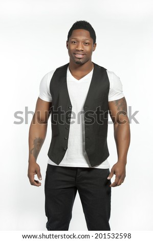Attractive African American male model wearing a black vest and black pants with a white t-shirt and vest posing in a studio on a white background while looking at the camera. - stock photo