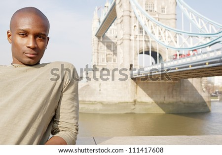 Attractive african american man standing by Tower Bridge in London being thoughtful and contemplating the city.
