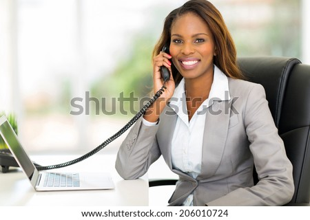 attractive african american office worker talking on the phone - stock photo