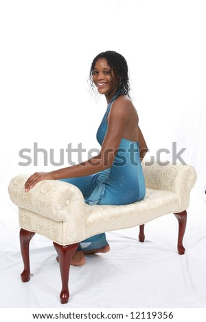 Attractive African American teen wearing a blue sparkly gown, sitting on an ivory bench against a white backdrop. - stock photo