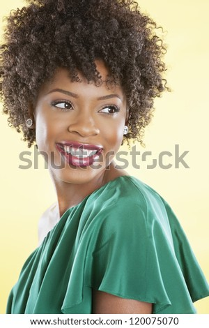 Attractive African American woman in an off shoulder dress looking away over colored background - stock photo