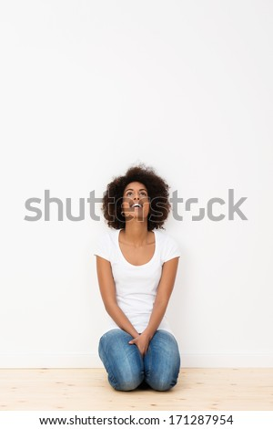 Attractive African American woman kneeling on the hardwood floor of her new house looking up into the air and laughing with pleasure, against an empty white wall with copyspace - stock photo