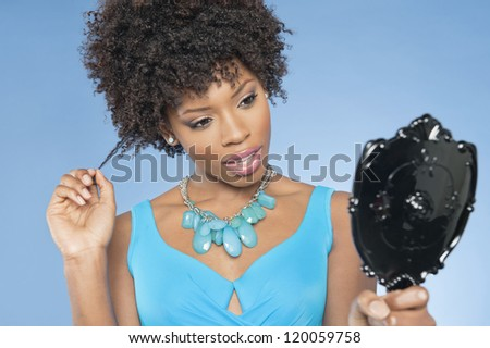 Attractive African American woman looking at herself in mirror over colored background - stock photo
