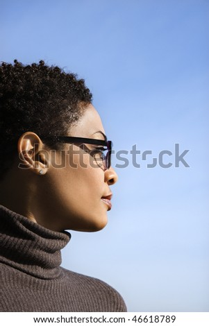 Attractive African American woman looks to the side against a blue sky background. Vertical shot. - stock photo
