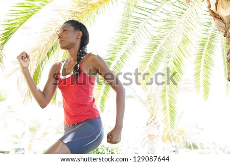 Attractive african american woman running in the city under a palm tree, training for fitness. - stock photo