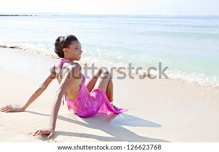 Attractive african american woman sitting on the beach by the shore with her feet getting bathed under the waves, contemplating the sea while on a tropical vacation. - stock photo