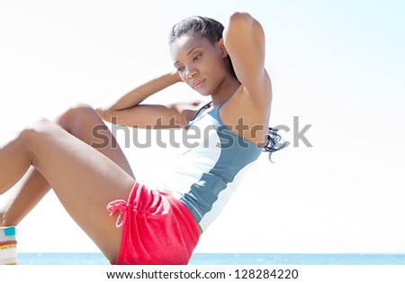 "Attractive ""african american"" working out and doing sit ups against a deep blue sky, exercising on a sunny day. - stock photo"