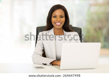attractive african businesswoman sitting in office - stock photo