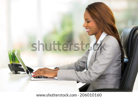 attractive african office worker using laptop computer - stock photo