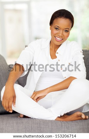 attractive african woman relaxing on a sofa - stock photo
