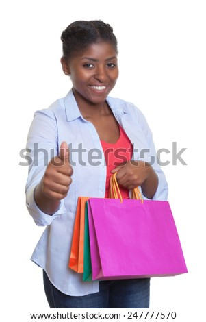 Attractive african woman with shopping bags showing thumb - stock photo