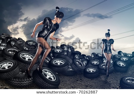 Attractive african women running on tires on the cloudy sky - stock photo