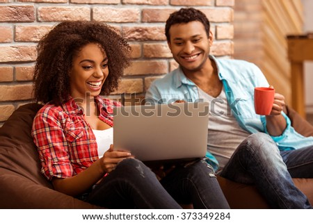 Attractive Afro-American couple using laptop, holding a cup and smiling while sitting on beanbag chairs against brick wall - stock photo