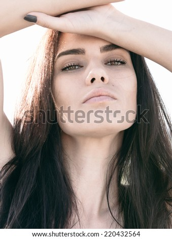 Attractive alluring young woman with a seductive expression, a lovely complexion and long brown hair looking at the camera with her hands raised to her forehead - stock photo