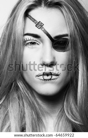 Attractive and beatiful blonde in black with abstract pirat make-up - stock photo