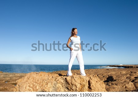 Attractive and confident mature woman standing on top of cliff overlooking ocean, isolated with blue sky as background and copy space.