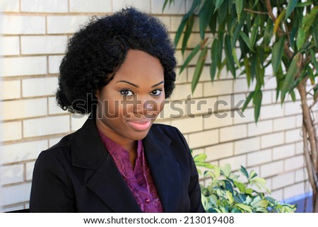 Attractive and Cute African American Business Woman Smiling and Looking At Camera While Wearing a Black Suit - stock photo