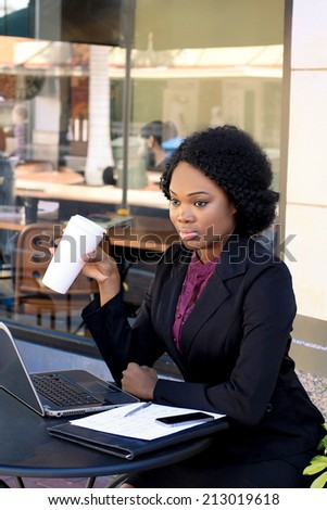 Attractive and Cute African American Business Woman Wearing a Black Suit and Working on a Laptop and Paperwork and Drinking Coffee - stock photo