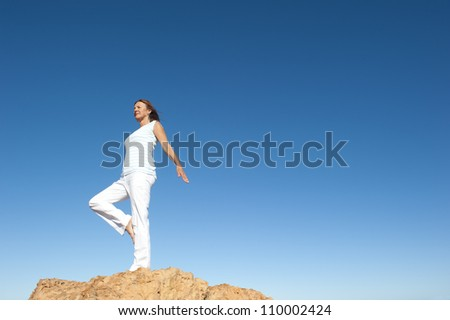 Attractive and fit mature woman standing confident and concentrated on top of a rock, balancing and exercising on one leg, isolated with blue sky as background and copy space. - stock photo