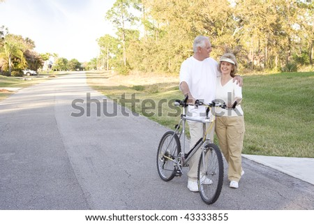 Attractive and fit seniors on bikes outdoors.