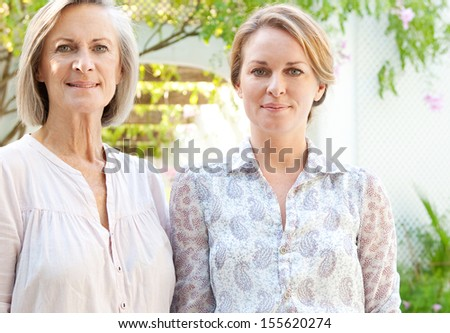 Attractive and happy adult daughter and mature mother standing together in their home garden next to each other and smiling at the camera, outdoors.