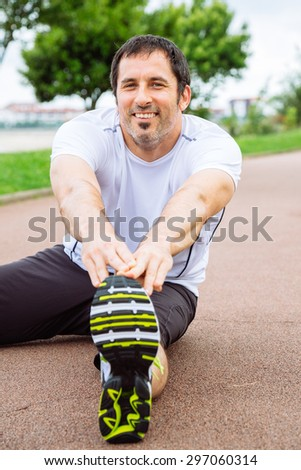 Attractive and happy spotrsman doing stretching exercises outdoors in a track - stock photo