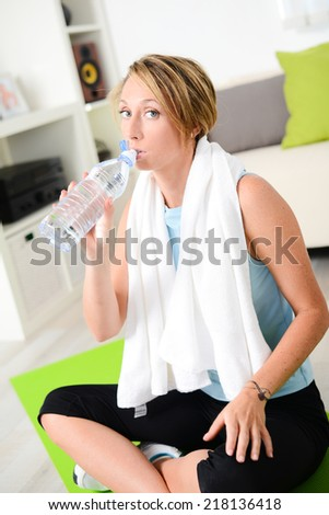 attractive and healthy lifestyle young woman drinking mineral water after a fitness exercises workout at home