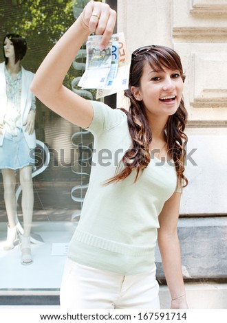 Attractive and joyful teenager girl showing off a bunch of bank notes bills money while standing by a fashion clothing store display window during a shopping day out in the mall, outdoors. - stock photo